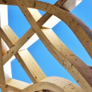 Curved timber beams against a blue sky
