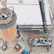 Round timber silo suspended from a crane, seen from above