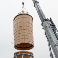 Round timber silo body dangling from a crane