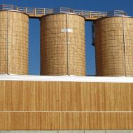 Complete facility integrated into a depot building in Eschlikon (Switzerland) consisting of three round timber silos and a timber roof platform