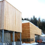 100 m³ timber modular silo with steel substructure, alongside a maintenance depot building with identical facade