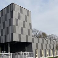 250 m³ architectural modular silo with timber facade in light and dark grey checks, visually integrated into a larger building complex