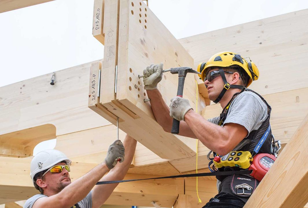 Two workers with helmets sit on a timber construction hammering in nails.