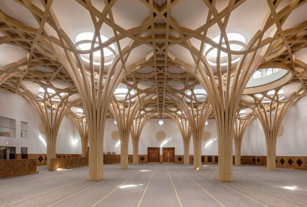 The interior is dominated by the tree-like wooden supporting structure. The skylights in the ceiling light up the vast space. The doors and individual details on the walls are designed in an oriental wooden structure.
