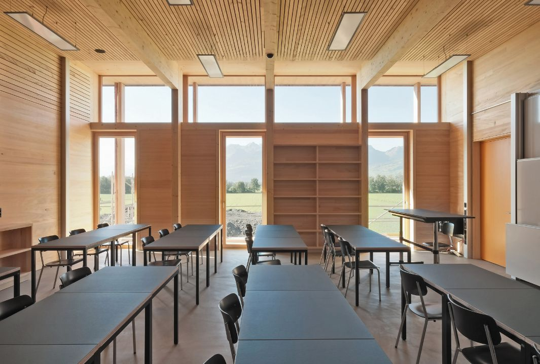 Classroom in the agricultural school in Salez with wooden shelves and a light wooden wall as well as a timber ceiling structure