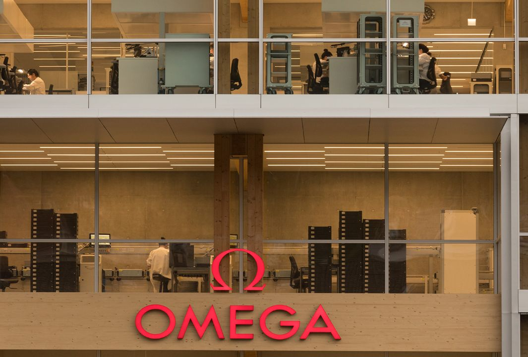 Large Omega lettering in red on the new timber office building with glazed front. In the background, personnel can be seen at their workstations.