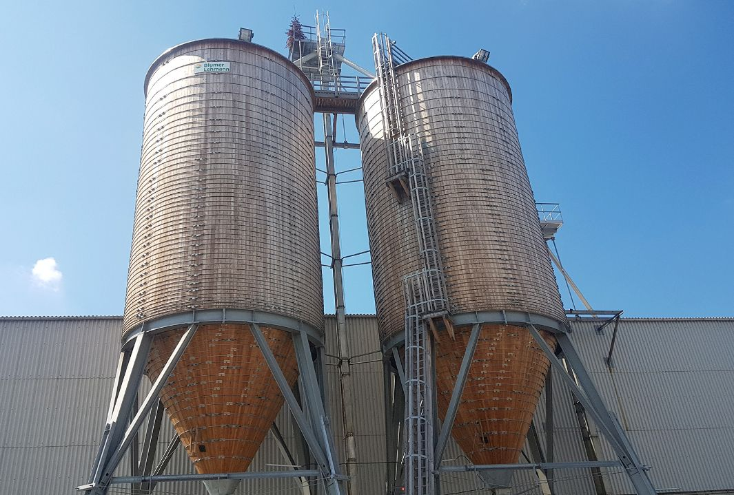 Two 600 m³ round timber silos with steel substructure and wooden ladder, connected by a timber roof platform, in front of an old industrial warehouse