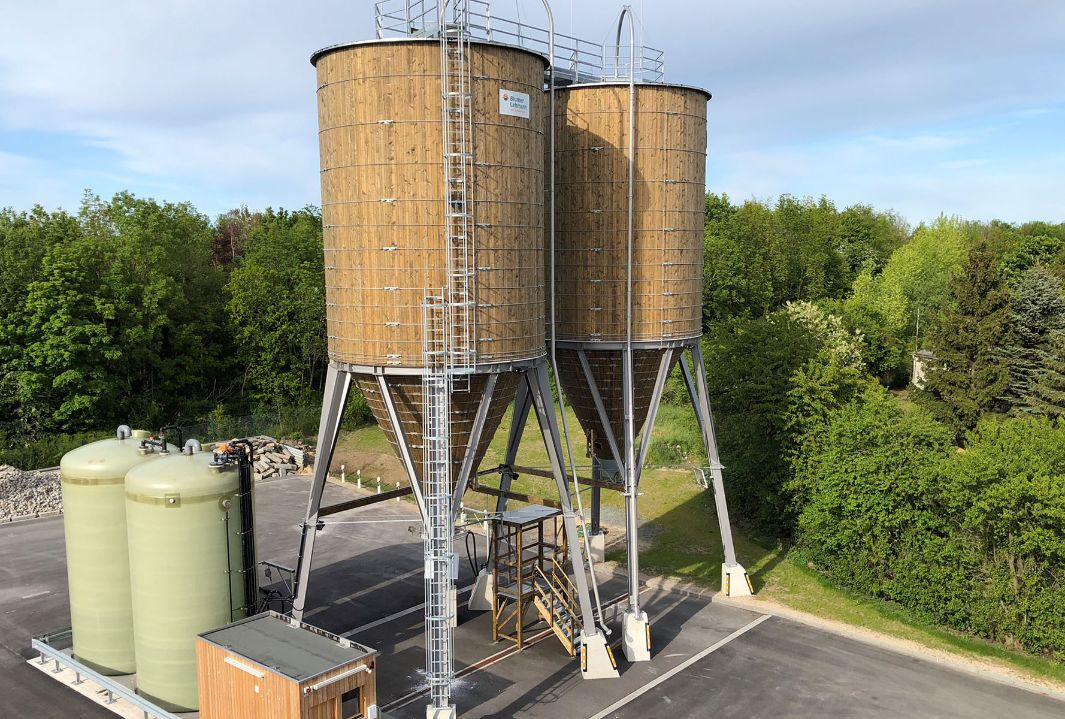 two 250 m³ round timber silos on steel substructure and brine technology, placed on a road maintenance depot