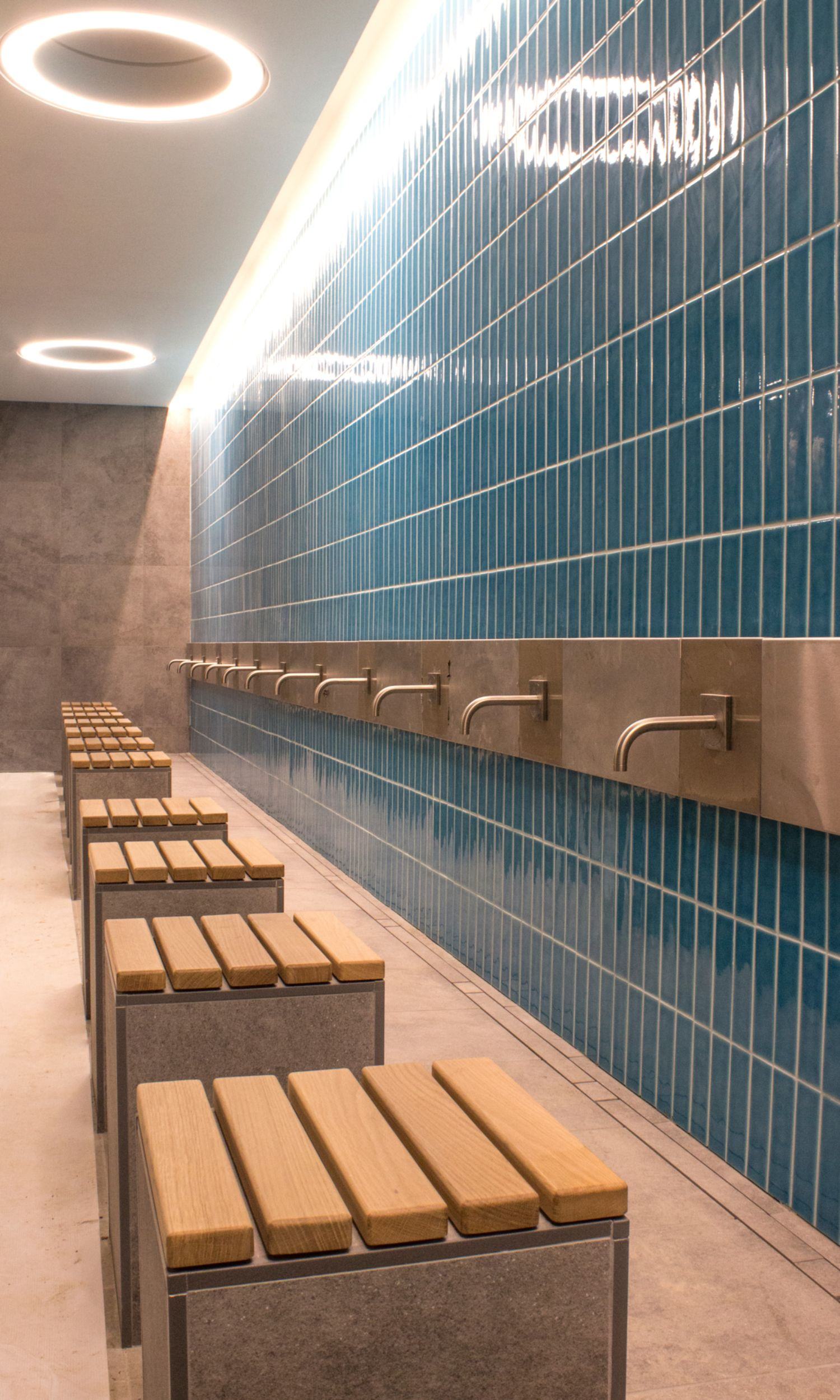 The photograph shows the washing area of the Cambridge Mosque. The stools are made of stone and clad with wooden panels. The taps are fixed to a blue slab wall.