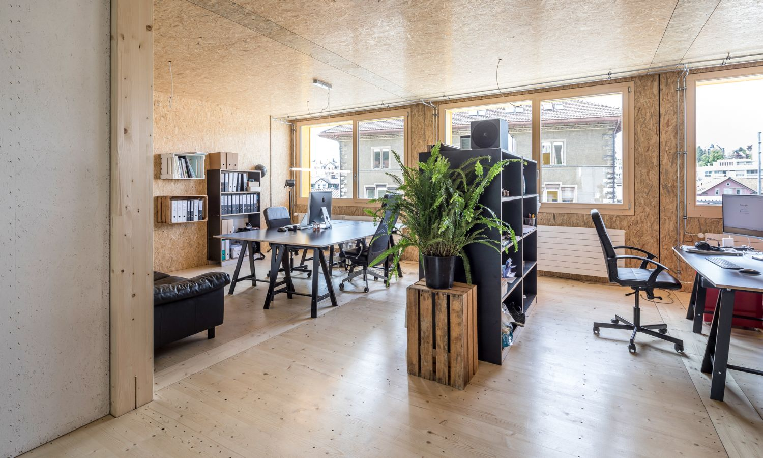 Photograph of an office interior finished entirely in wood with modern furnishing in the Lattich building in St. Gallen