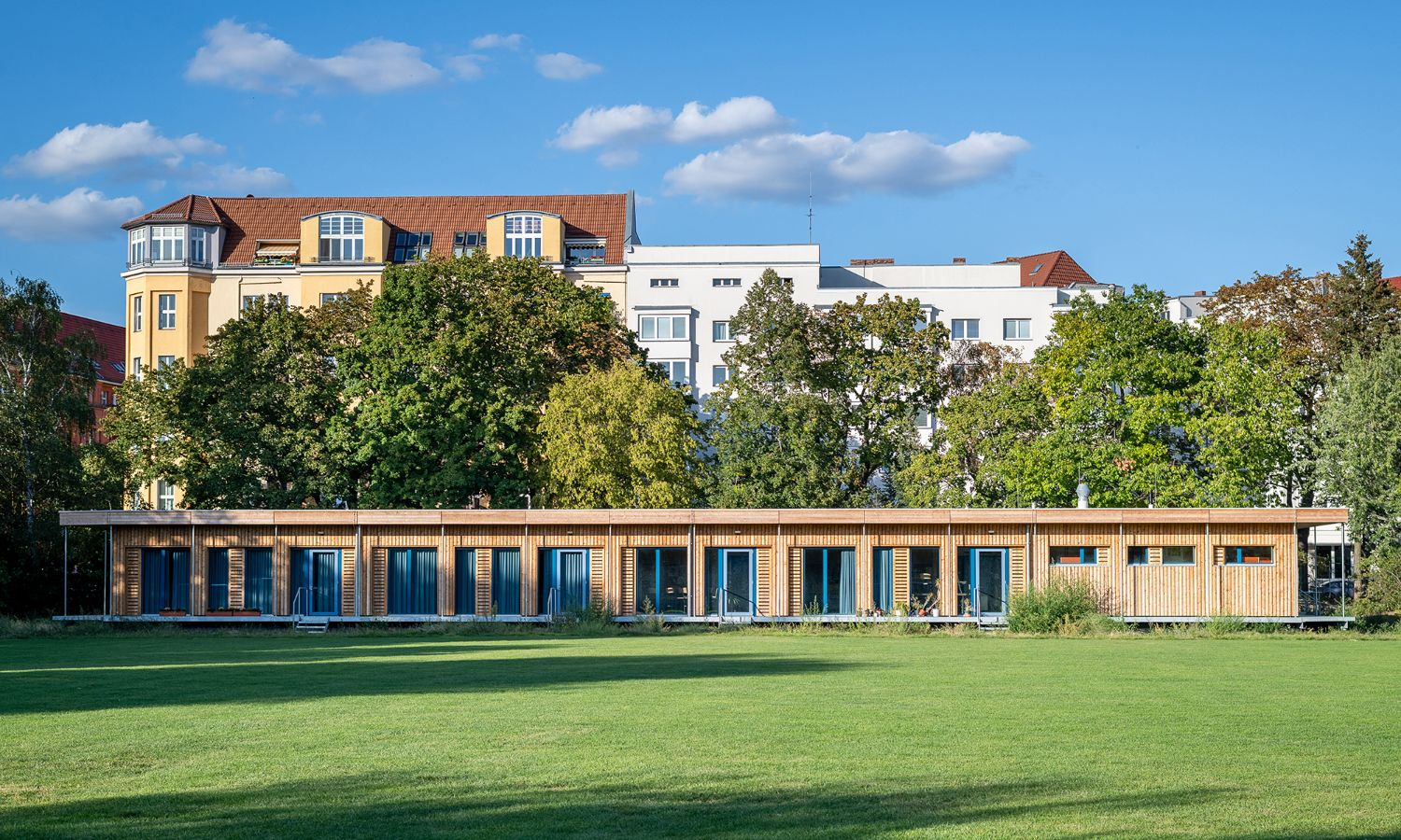 Visualisation of a single-storey, temporary school building in Berlin Schönefeld. The wooden facade stands out against the green meadow and blue sky.
