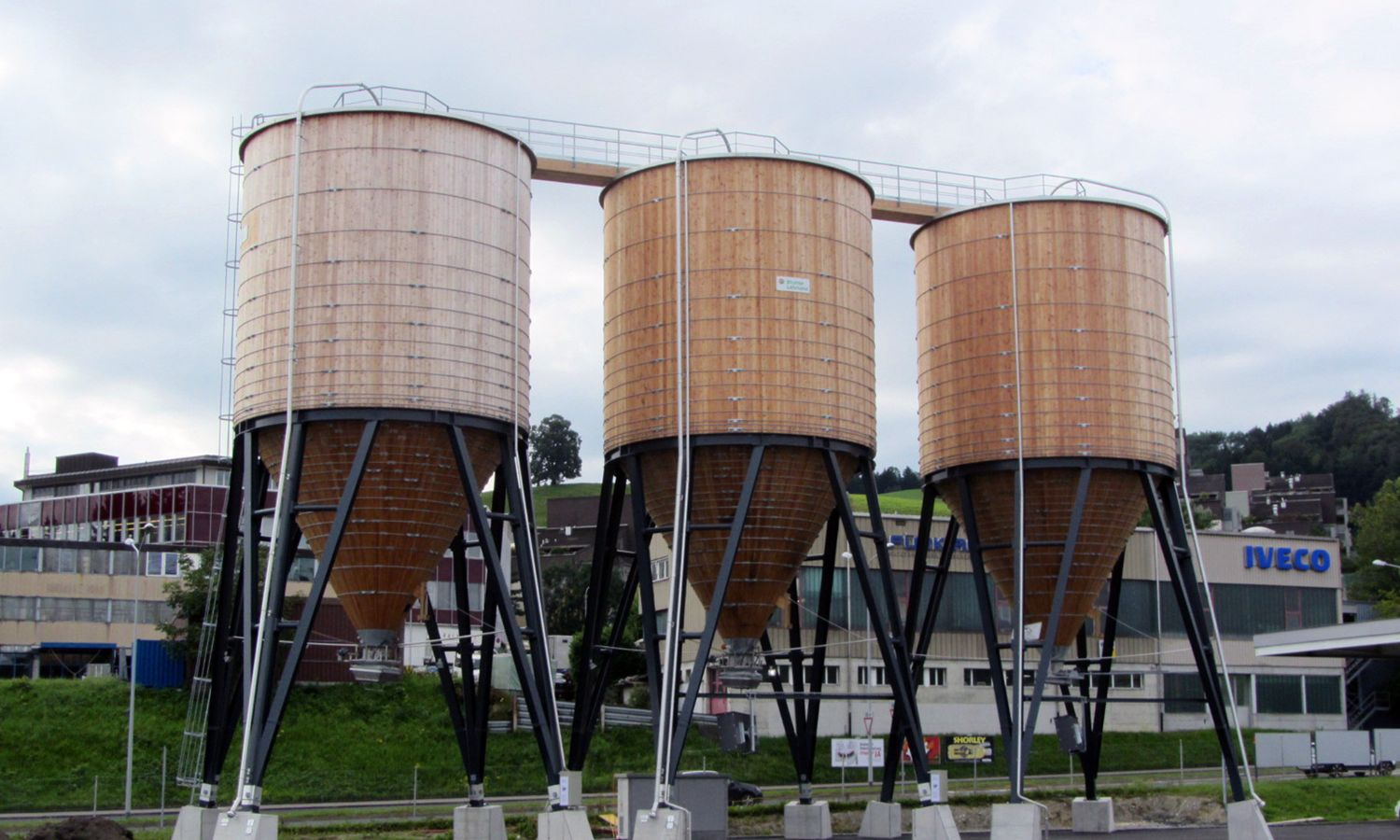 Three round timber silos in a line, connected by a roof crossover, St Gallen Neudorf