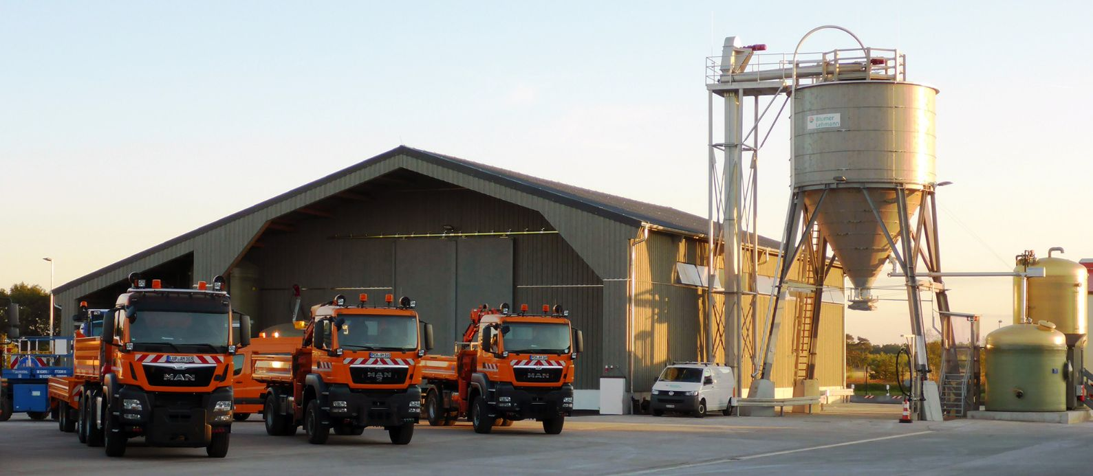 Complete facility in Fahrbinde (DE), comprising a storage depot, a timber silo and a brine facility, with three winter service vehicles parked in front