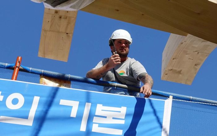 Carpenter/installer on an international construction site holding a radio