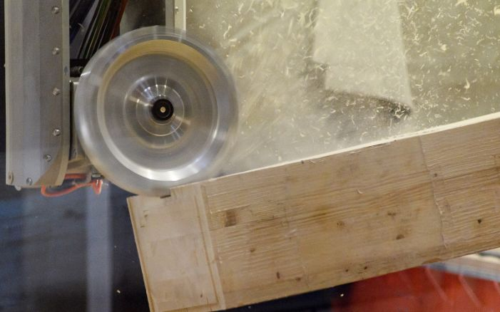 The milling head processes the piece of wood on the CNC machine. The shavings fly off.