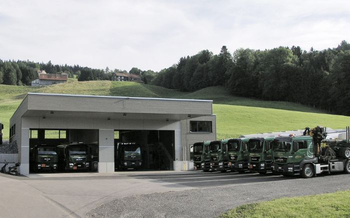Overall view of the lorry garage with the lorry fleet parked in front.