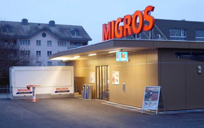A single-storey temporary timber construction at dusk with the Migros neon sign on the roof.