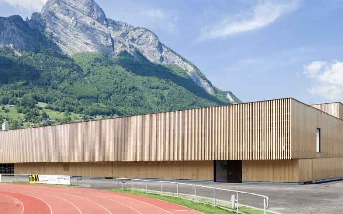RSA Sargans sports hall with tartan track in the foreground and mountain backdrop.