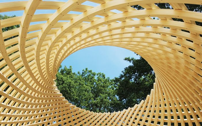 Green views through an opening in a free-form timber pavilion