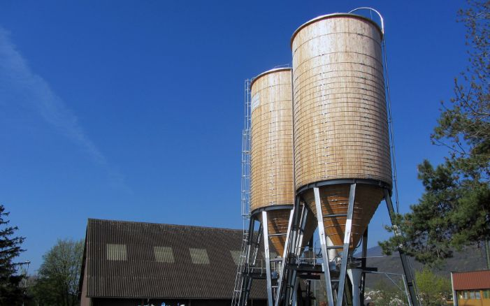 Two 400 m³ round timber silos with steel ladder and grey steel substructure, in front of a barn