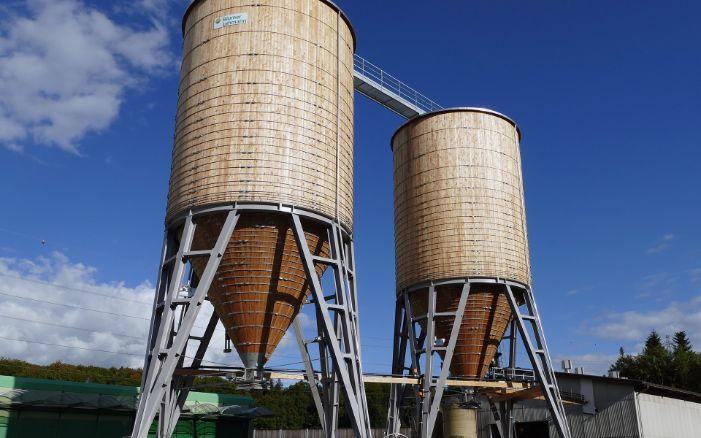 Two 500 m³ round timber silos with black steel substructure on concrete base, at a maintenance depot